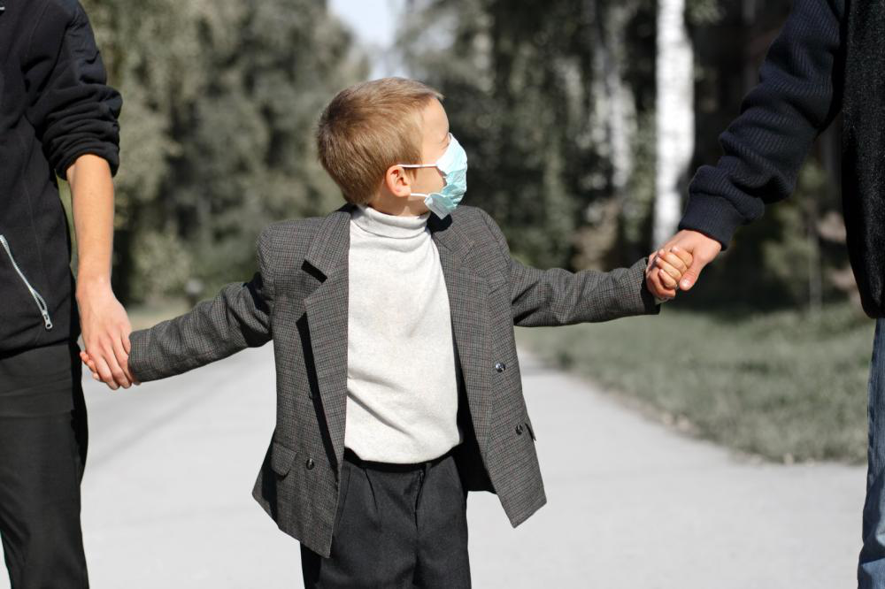 A small boy with winter flu accompanying his parents to a pediatrician clinic.