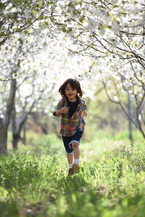 Boy Running Through A Grassy Field