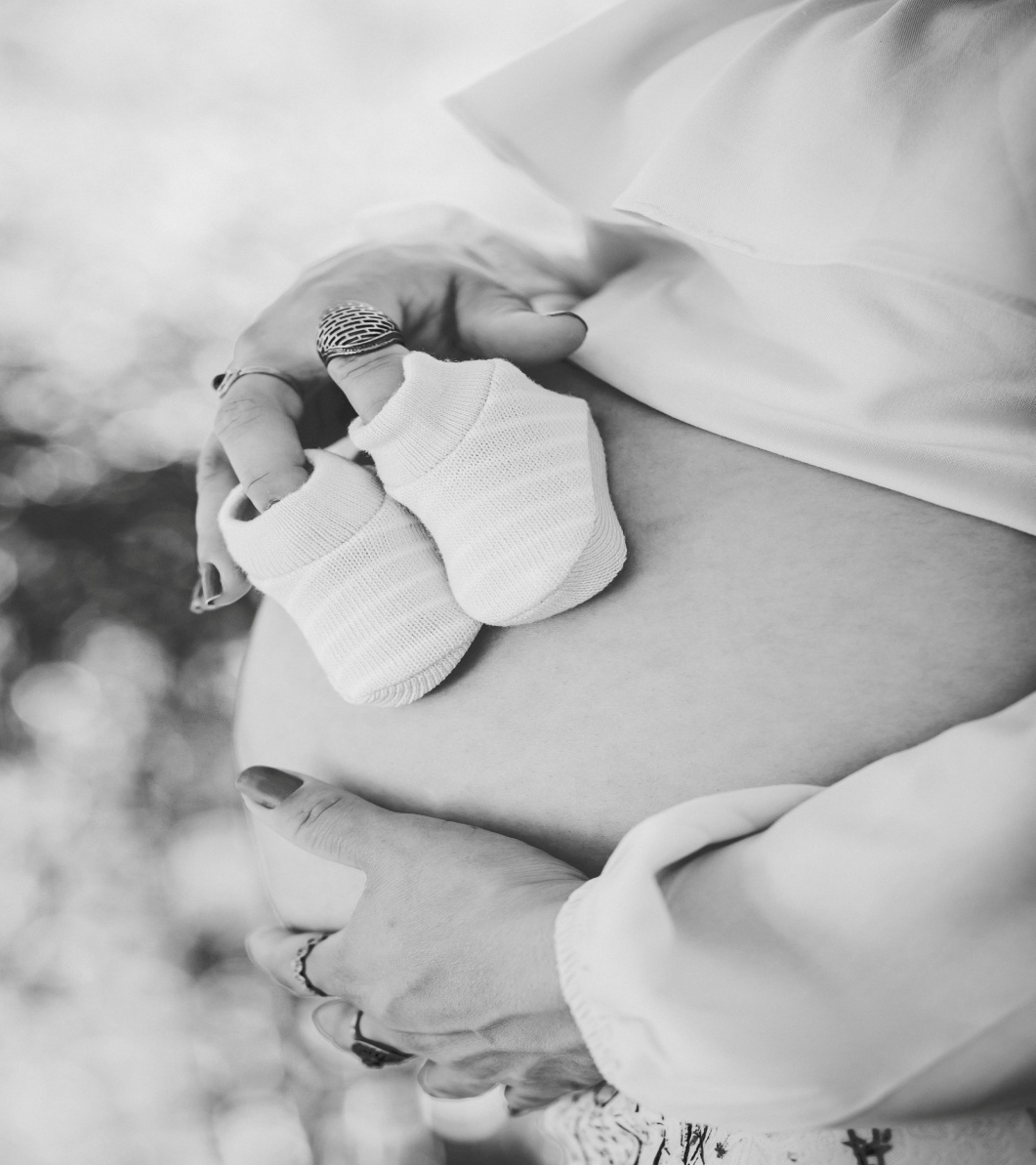 Grayscale photo of a pregnant belly
