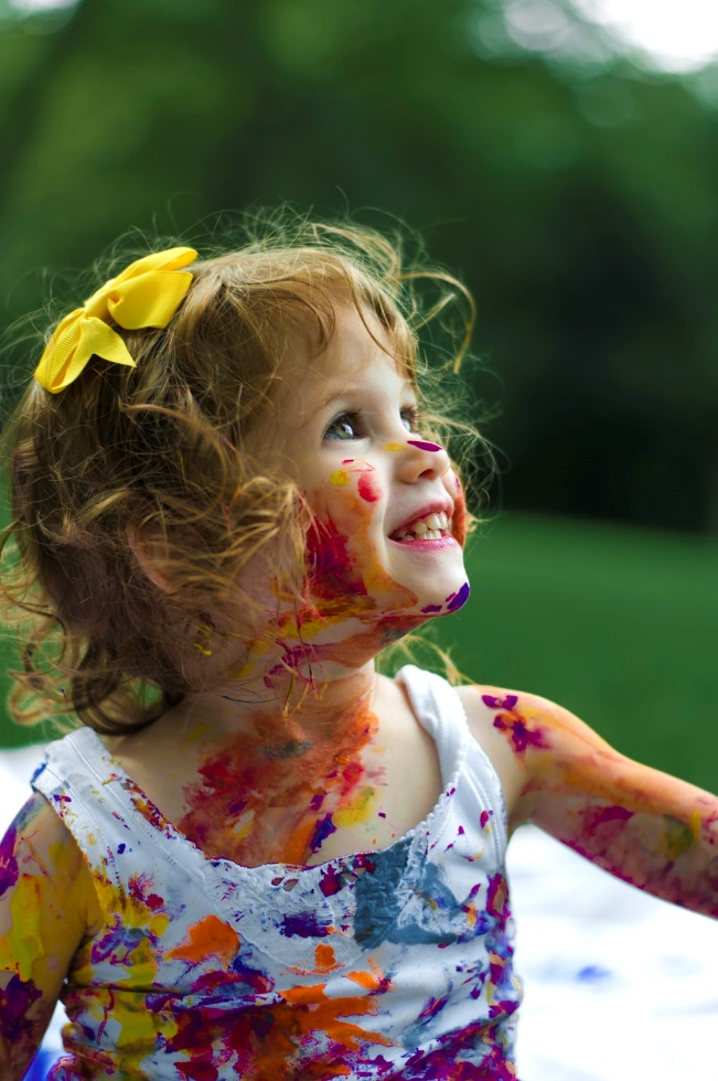 A happy child covered in paint