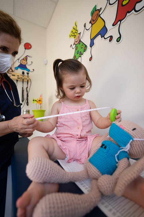 A child playing while being observed by a doctor